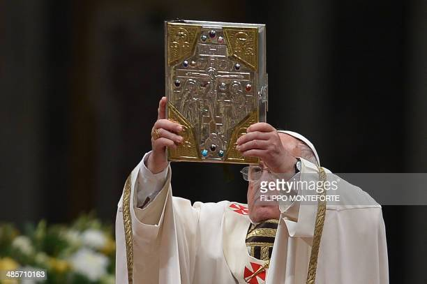 Pope Francis lifts up the book of Gospels during the Easter Vigil at the St Peter basilica in Vatican. Easter Vigil, also called the Paschal Vigil is...