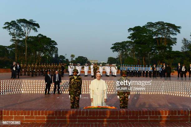 Pope Francis looks on after laying a floral wreath at the National Martyrs' memorial of Bangladesh in Savar some 30 km from Dhaka on November 30 2017...