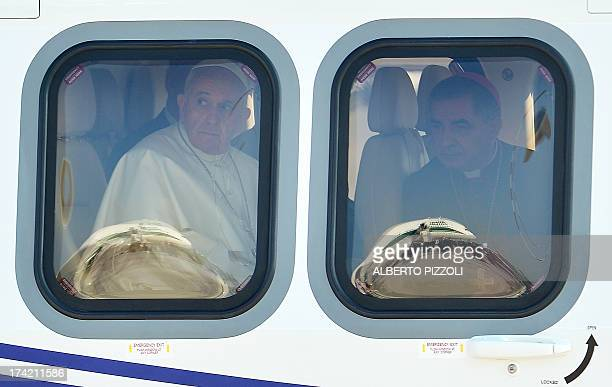 Pope Francis looks out from the helicopter as arrives to board a plane on July 22 2013 at Rome's Fiumicino airport on his way to his first overseas...