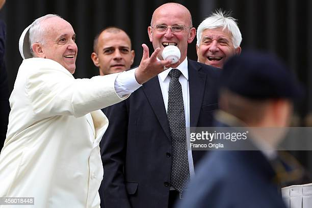 Pope Francis loses his 'papalina' cup as he catches a baseball ball thrown by a faithful at the end of his weekly audience at St Peter's Square on...