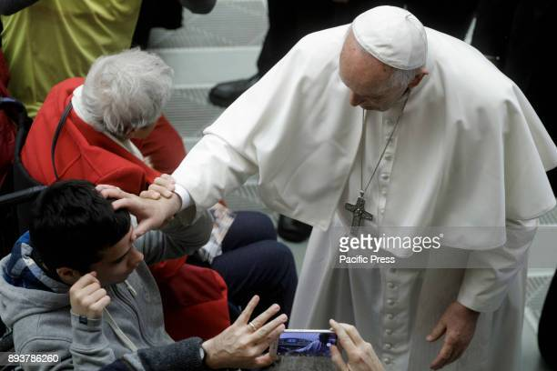 Pope Francis makes a cross sign on a boys forehead during the Weekly General Audience in Paul VI Hall in Vatican City Vatican