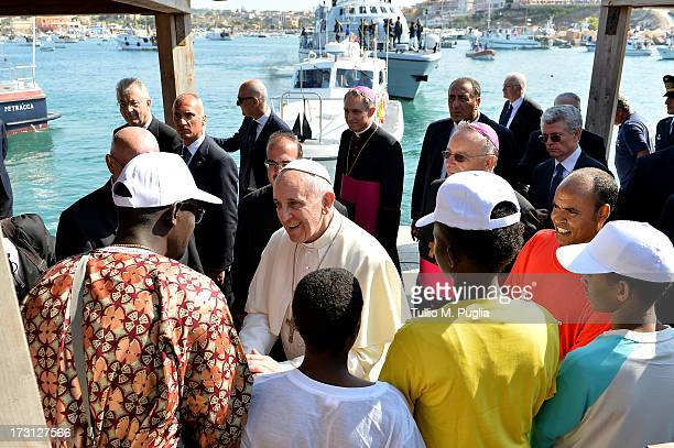 Pope Francis meets a group of immigrants at the pier of the island on July 8, 2013 in Lampedusa, Italy. On his first official trip outside Rome, Pope...