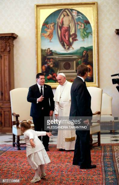 Pope Francis meets with Paraguay's President Horacio Cartes as his niece Sofia plays during a private audience at the Vatican on November 9 2017 /...