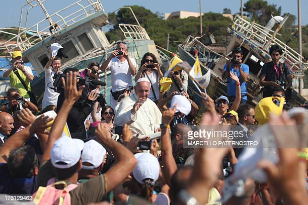 Pope Francis passes by remains of migrants boats as he waves upon arrival during his visit to the island of Lampedusa a key destination of tens of...