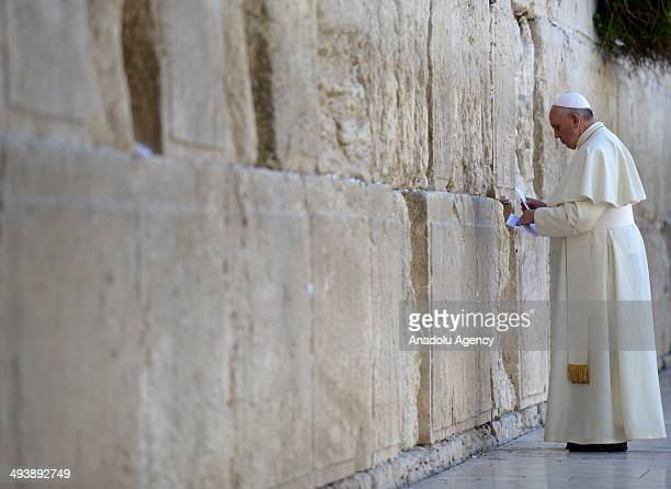 Pope Francis places a prayer paper at the Western Wall Judaism's holiest site in the Old City of Jerusalem on May 26 2014 The Vatican's Pope Francis...