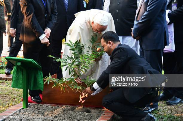 Pope Francis plants a tree during his visit to the National Martyrs' memorial of Bangladesh in Savar some 30 km from Dhaka on November 30 2017 Pope...