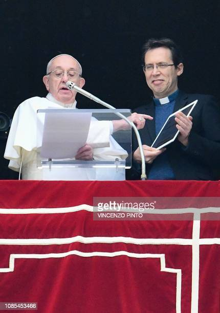 Pope Francis points to a tablet computer as he invites the faithful to download the 'Click to Pray' app from the window of the Apostolic Palace...