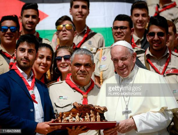 Pope Francis poses with a group of the Terra Sancta Scout Troop Bethlehem at the end of the weekly general audience on June 12 2019 at St Peter's...