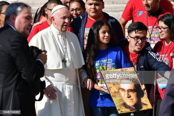 Pope Francis poses with youth from USbased immigrant rights National TPS Alliance group and a group's girl holding a portrait of slain Salvadorian...