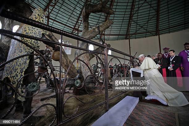 Pope Francis prays at the Namugongo Martyrs' Shrine in Namugongo Uganda on November 28 2015 Pope Francis arrived in Uganda on November 27 on the...