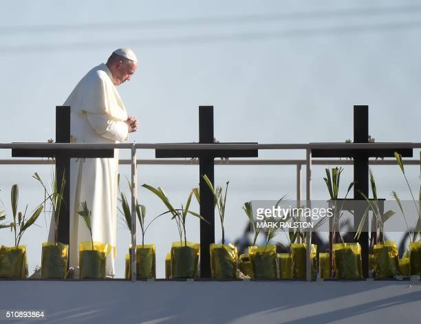 TOPSHOT Pope Francis prays besides crosses on a platform in Mexico those who died trying to cross the border at El Paso Texas on February 17 2016...