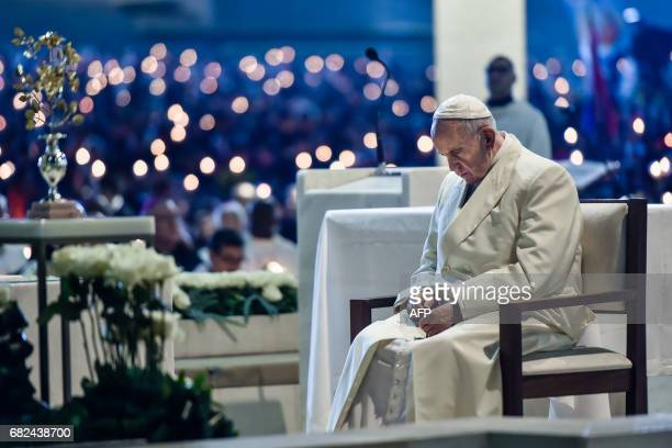 Pope Francis prays during the Blessing for the Candles from the Chapel of the Apparitions in Fatima on May 12 2017 Two of the three child shepherds...