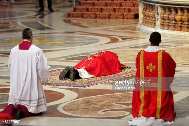 Pope Francis prays on the floor during a Papal Mass with the Celebration of the Lord's Passion inside St Peter's Basilica on April 18 2014 in Vatican...
