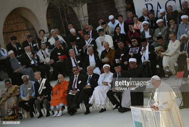Pope Francis reads his speech in front of representatives from different religious traditions in the square outdoor the St Francis basilica in Assisi...