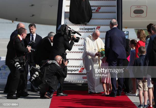 Pope Francis receives a bouquet of flowers from fiveyearold Annalise daughter of Foreign Affairs minister Simon Coveney as he arrives at Dublin...