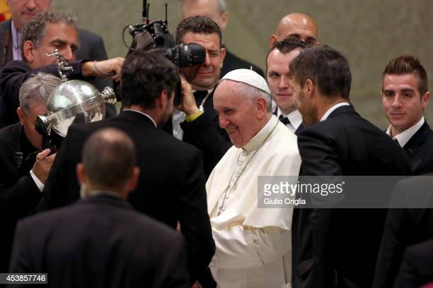 Pope Francis receives the Copa Libertadores trophy from Matias Lammens as he meets members of the San Lorenzo football team during his weekly public...
