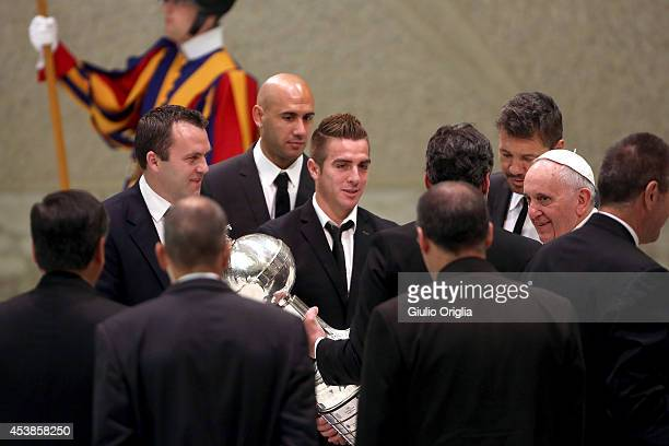 Pope Francis receives the Copa Libertadores trophy from President Matias Lammens as he meets members of the San Lorenzo football team during his...