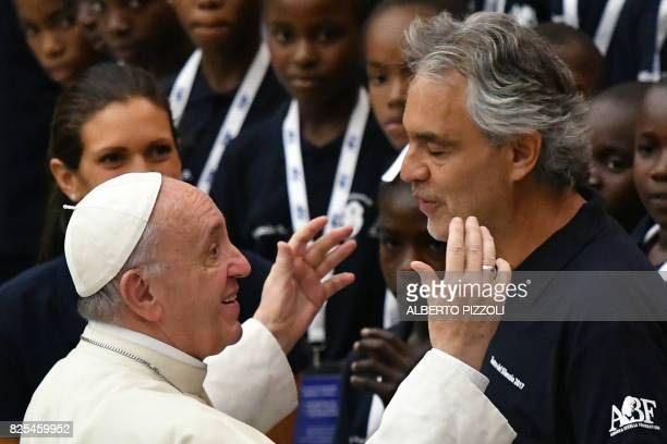 Pope Francis salutes Italian tenor Andrea Bocellias as members of the Andrea Bocelli Foundation 'Voices of Haiti' choir look on during the weekly...