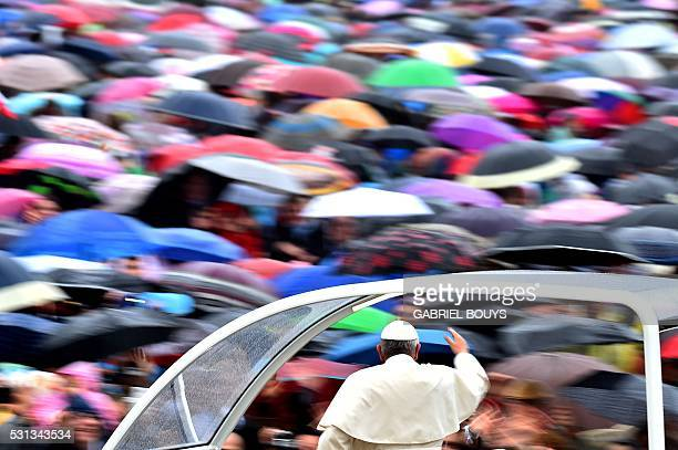 TOPSHOT Pope Francis salutes the crowd as he arrives for a Jubilee Audience in St Peter's Square at the Vatican on May 14 2016 / AFP / GABRIEL BOUYS