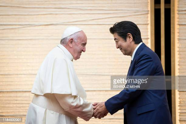 Pope Francis shakes hands with Japan's Prime Minister Shinzo Abe during a meeting with the diplomatic community at the prime minister's office in...