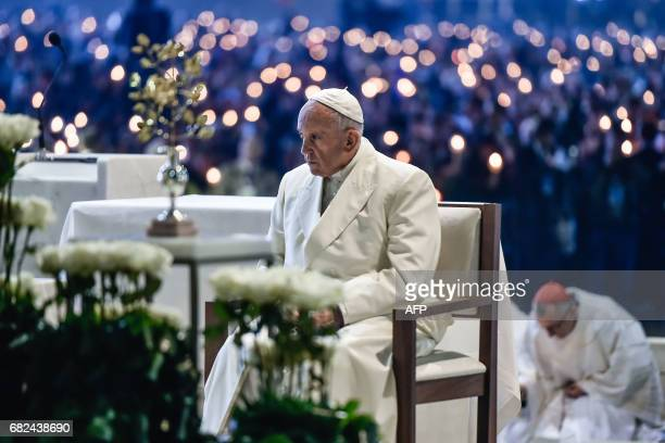 Pope Francis sits during the Blessing for the Candles from the Chapel of the Apparitions in Fatima on May 12 2017 Two of the three child shepherds...