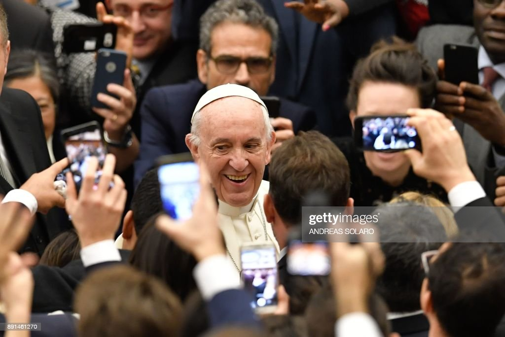 Pope Francis smiles as he arrives for his weekly general audience at the Paul VI audience hall on December 13, 2017 at the Vatican. / AFP PHOTO / Andreas SOLARO