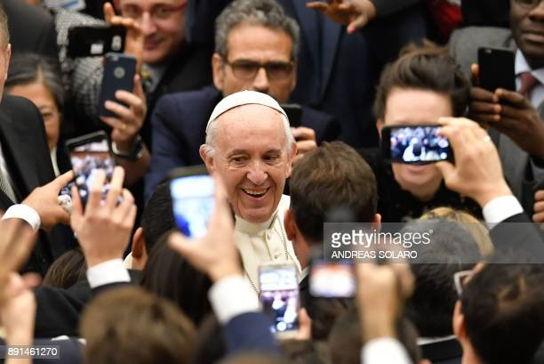 Pope Francis smiles as he arrives for his weekly general audience at the Paul VI audience hall on December 13 2017 at the Vatican / AFP PHOTO /...