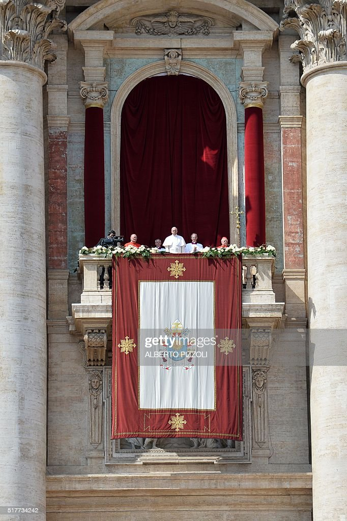 Pope Francis (C) stands at the central loggia of St Peters' basilica to deliver the 'Urbi et Orbi' blessing for Rome and the world following the Easter Sunday mass on March 27, 2016 at St Peter's square in Vatican. Christians around the world are marking the Holy Week, commemorating the crucifixion of Jesus Christ, leading up to his resurrection on Easter.