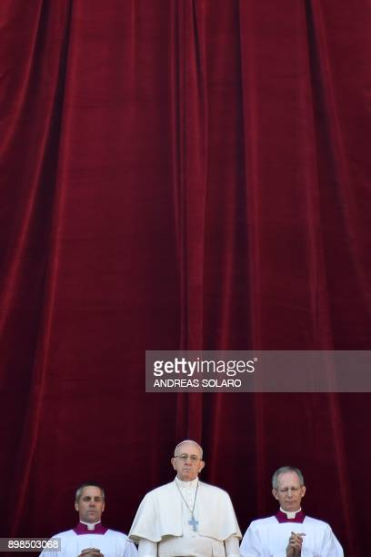 Pope Francis stands from the balcony of St Peter's basilica during the traditional Urbi et Orbi Christmas address and blessing given to the city of...