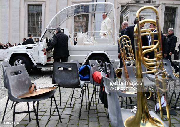 Pope Francis stands in the popemobile as he leaves St Peters square at the Vatican at the end of his weekly general audience on March 21 2018 / AFP...