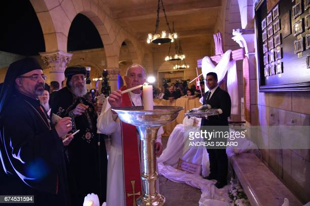 Pope Francis stands next to Coptic Pope Tawadros II as he lights a candle during a visit at the Saint Peter and Saint Paul church in Cairo which was...