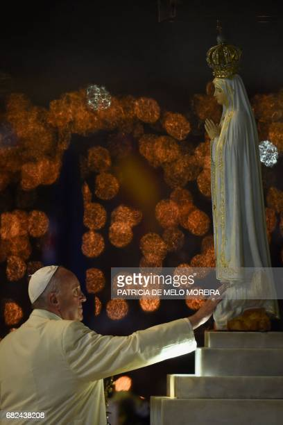 Pope Francis touches a figure representing Our Lady of Fatima during the Blessing for the Candles from the Chapel of the Apparitions in Fatima on May...