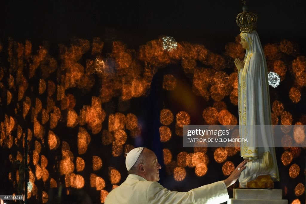 TOPSHOT - Pope Francis touches a figure representing Our Lady of Fatima during the Blessing for the Candles from the Chapel of the Apparitions, in Fatima on May 12, 2017. Two of the three child shepherds who reported apparitions of the Virgin Mary in Fatima, Portugal, one century ago, will be declared saints on May 13, 2017 by Pope Francis. The canonisation of Jacinta and Francisco Marto will take place during the Argentinian pontiff's visit to a Catholic shrine visited by millions of pilgrims every year. /