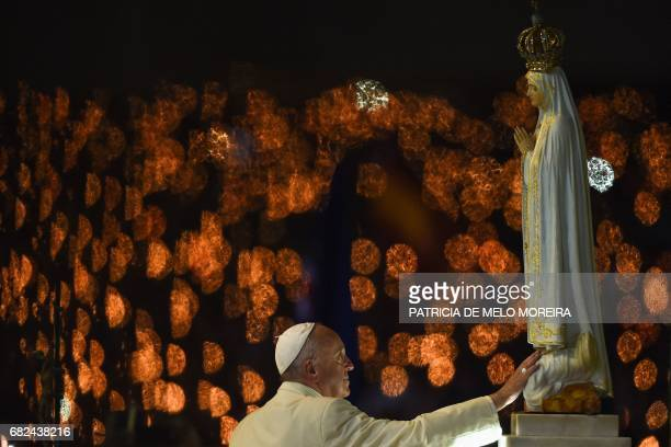 TOPSHOT Pope Francis touches a figure representing Our Lady of Fatima during the Blessing for the Candles from the Chapel of the Apparitions in...