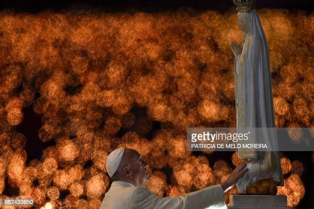 Pope Francis touches the figure representing Our Lady of Fatima during his visit to the Chapel of the Apparitions at the Fatima shrine in Fatima on...