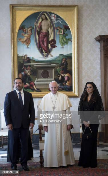 Pope Francis walks along with Prime Minister of Lebanon Saad Hariri and his wife Lara during a private audience at the Vatican on October 13 2017 /...