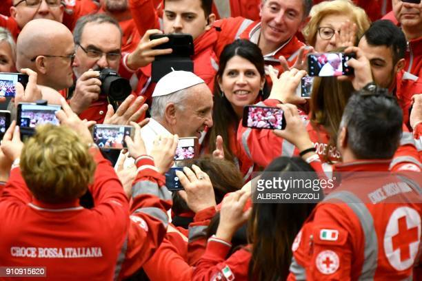 Pope Francis walks among members of the Italian Red Cross and Red Crescent during an audience in the Paul VI hall at the Vatican on January 27 2018 /...
