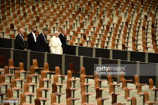 Pope Francis walks through empty chairs as he arrives to hold a limited public audience inside Paul VI Hall at the Vatican on October 7 during the...
