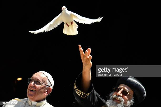 Pope Francis watches as Egypt's Coptic Orthodox Pope Tawadros II releases a dove after a meeting with other religious leaders at the Pontifical...