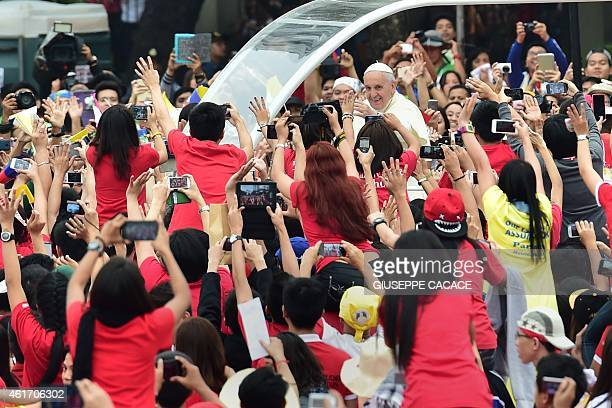 Pope Francis waves as he arrives at the University of Santo Tomas during his visit to Manila on January 18 2015 Pope Francis later celebrated mass...