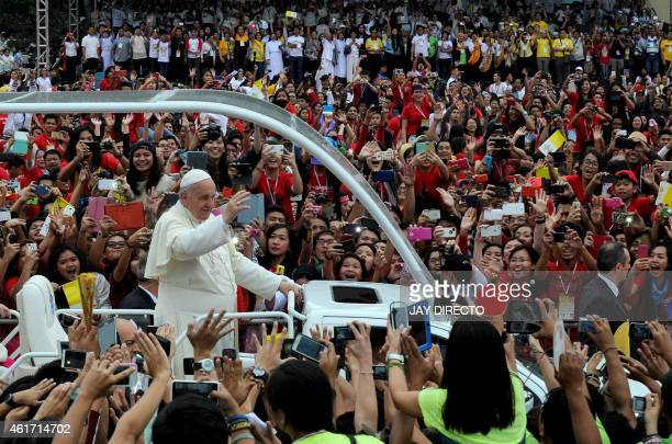 Pope Francis waves as he arrives at the University of Santo Tomas during his visit to Manila on January 18 2015 Pope Francis celebrated mass with...