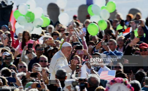 Pope Francis waves as he arrives in St Peter's Square at the Vatican for his weekly general audience on September 20 2017 / AFP PHOTO / VINCENZO PINTO