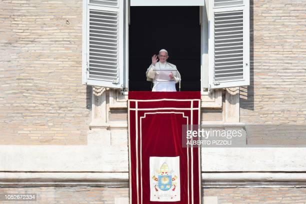 Pope Francis waves as he arrives to address the faithful from the window of the apostolic palace overlooking StPeter's square during the weekly...
