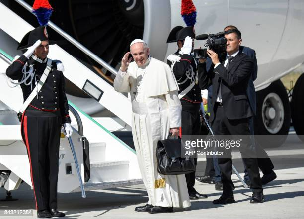 TOPSHOT Pope Francis waves as he boards an aircraft at Fiumicino International Airport in Rome on September 6 as he prepares to travel to Colombia...