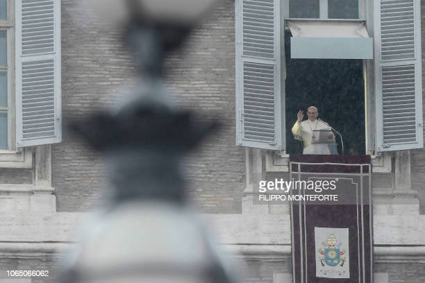Pope Francis waves as he delivers his message to the faithful during the weekly Angelus prayer on November 25 2018 as rain pours over St Peter's...
