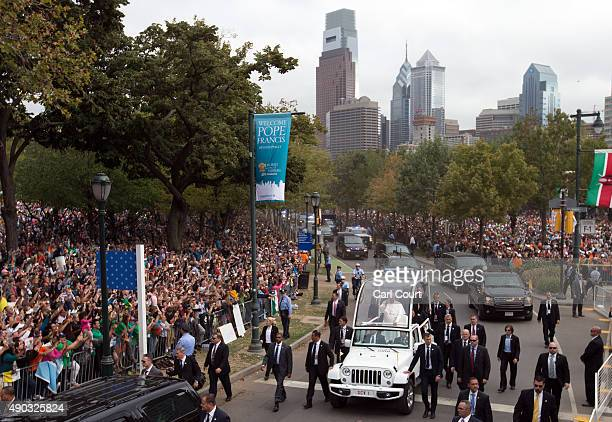 Pope Francis waves as he drives along Benjamin Franklin Parkway to lead Mass on September 27 2015 in Philadelphia Pennsylvania Pope Francis is on the...