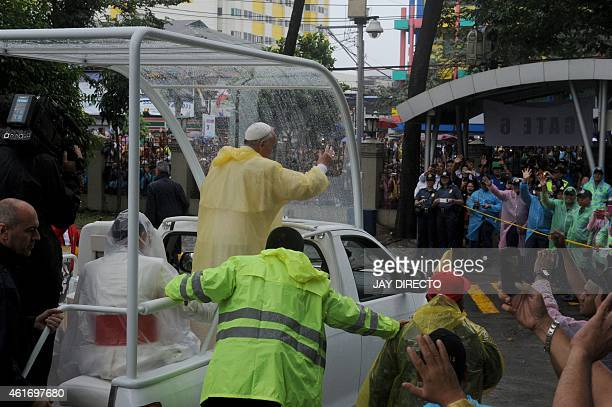Pope Francis waves as he leaves following his visit to the University of Santo Tomas in Manila on January 18 2015 Pope Francis will celebrate mass...