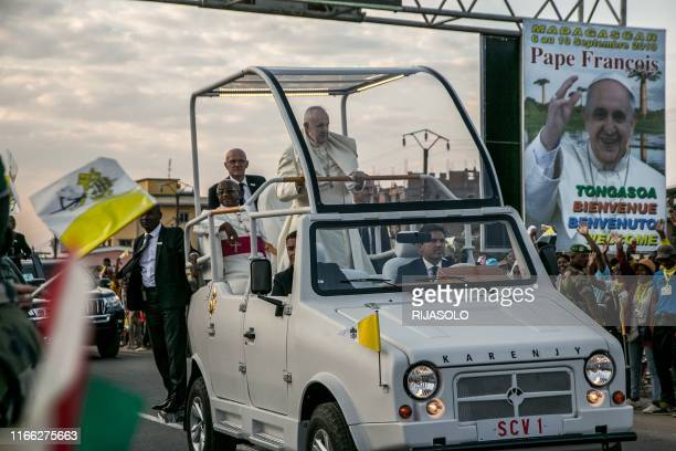 Pope Francis waves as he passes aboard his papamobile, a Karenjy Mazana II made in Madagascar especially for his visit, during his official visit to...