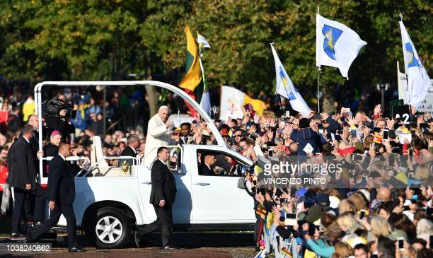 Pope Francis waves as he travels among crowds of followers as he arrives to take part in an openair mass at Santakos Park in Kaunas on September 23...