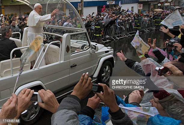 Pope Francis waves at faithfuls from the popemobile after giving a mass at the Basilica of Our Lady of Aparecida Brazil's most revered Catholic...